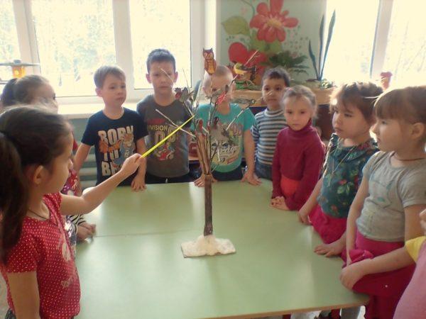 Дети рассматривают модель дерева с птичками