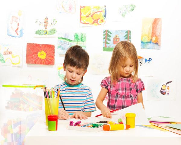 Мальчик и девочка рисуют цветными карандашами