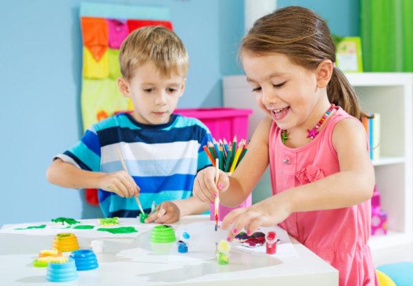 Мальчик и девочка рисуют красками и карандашами