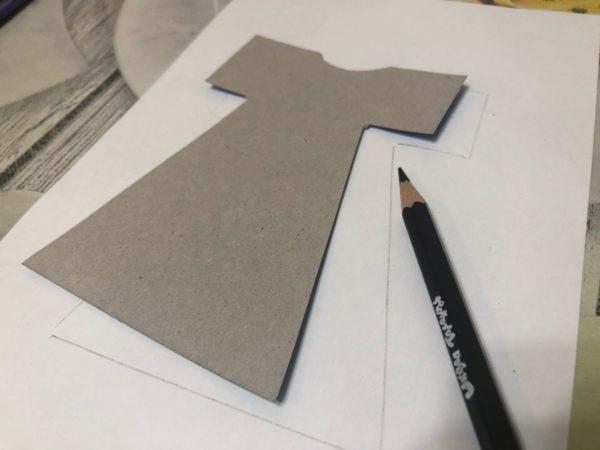 Картонный шаблон платья, обведённый карандашом на бумаге
