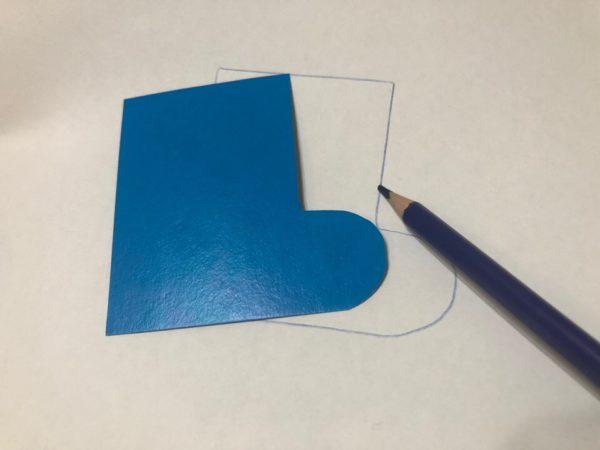 Картонный шаблон сапожка обведён карандашом на бумаге