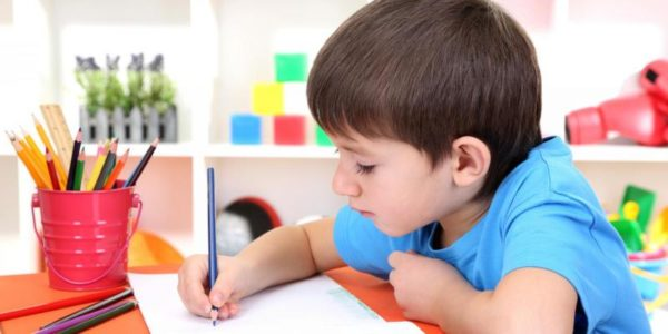 Мальчик в синей футболке рисует