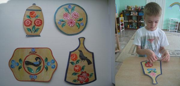 Дидактическая игра «Укрась посуду»; мальчик выкладывает на картонной доске элементы городецкой росписи