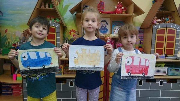 Трое детей держат рисунки автобусов