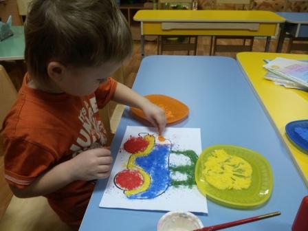 Мальчик пальцами раскрашивает машинку