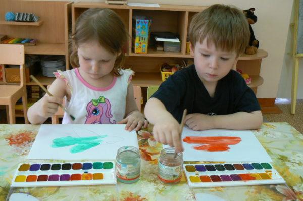 Мальчик и девочка рисуют акварельными красками