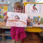 Девочка держит рисунок снегиря ватными палочками