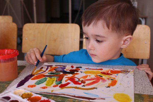 Мальчик рисует красками