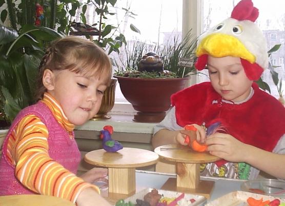 Дети лепят петушков, один ребёнок украшает хвост настоящими перьями