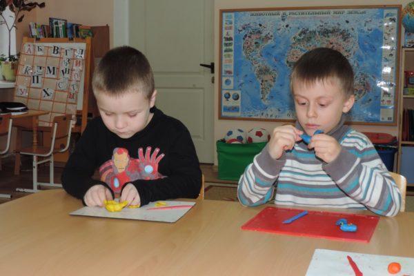 Два мальчика лепят из пластилина