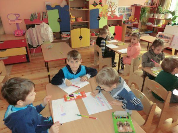 Дети за столами рисуют автобусы