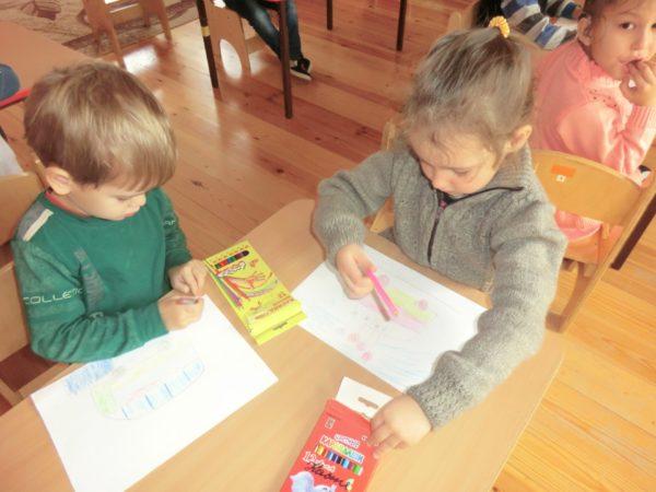 Мальчик и девочка за столом рисуют автобусы