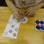 Ребёнок с помощью ватной палочки украшает валенки узором