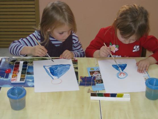 Две девочки рисуют девочек в синих платьях