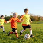 Мальчики и девочки играют в футбол