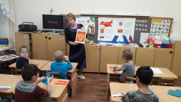 Педагог показывает детям герб России