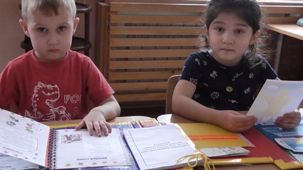 Мальчик и девочка работают с лэпбуком