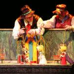 Два клоуна-кукловода держат кукол королевской семьи