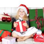 Девочка в колпаке Деда Мороза с подарками в руках