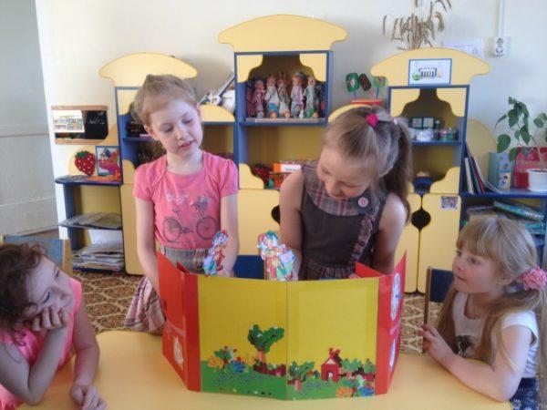 Девочки ставят кукольную постановку, используя лэпбук в качестве ширмы