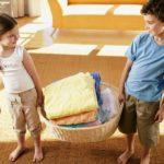 Мальчик и девочка несут корзину с бельём