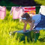 Девочка развешивает стиранное бельё
