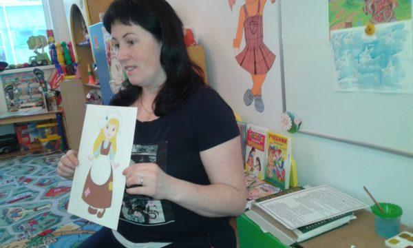 Педагог держит в руках изображение Золушки