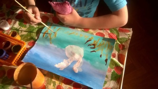 Ребёнок рисует белого лебедя на тонированной основе (два оттенка голубого)