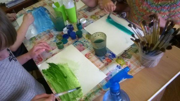 Дошкольники тонируют основу для рисования