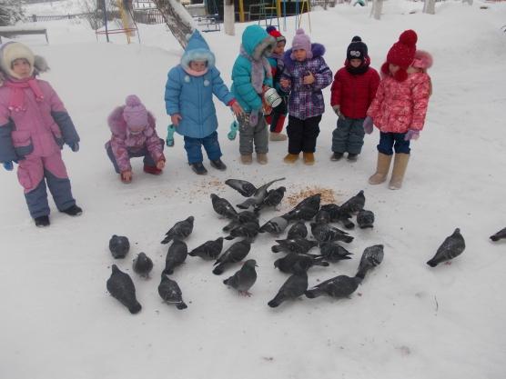 Дошкольники на прогулке кормят голубей