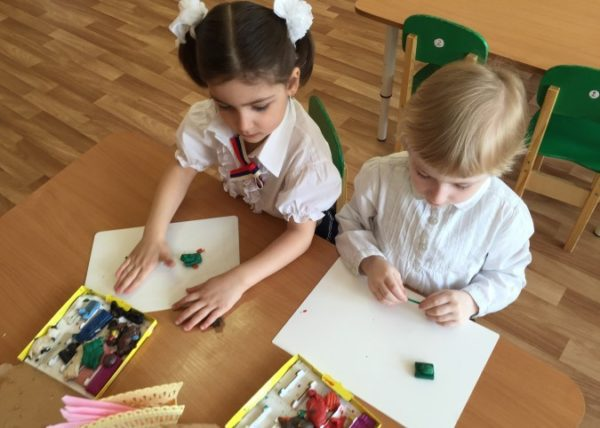 Дошкольники занимаются с пластилином на занятии
