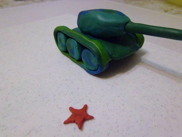 Полоска намотана на колёса, рядом с танком лежит звезда из красного пластилина
