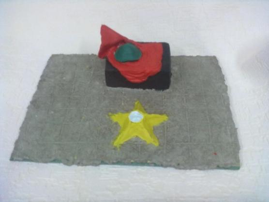 Вечный огонь, позади него на постаменте лежит красное знамя и солдатская каска