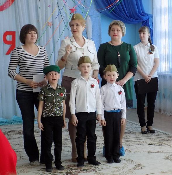 Поющее трио мальчиков и педагоги, стоящие за исполнителями