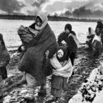 Женщины и дети идут по заснеженной местности