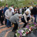 Люди в День Победы возлагают цветы к памятнику