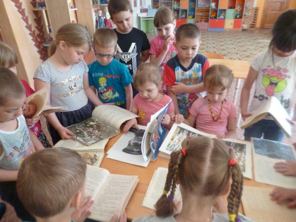 Дети у стола рассматривают книги, картинки о войне