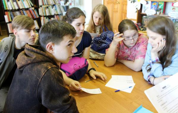 Подростки за столом выполняют задание