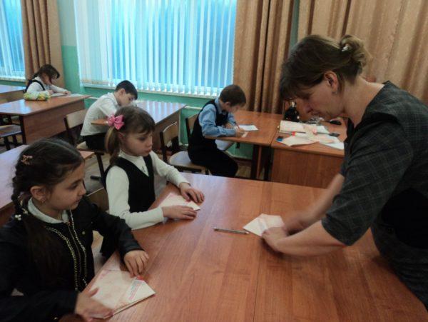 Учительница показывает, как сделать треугольник письма на фронт