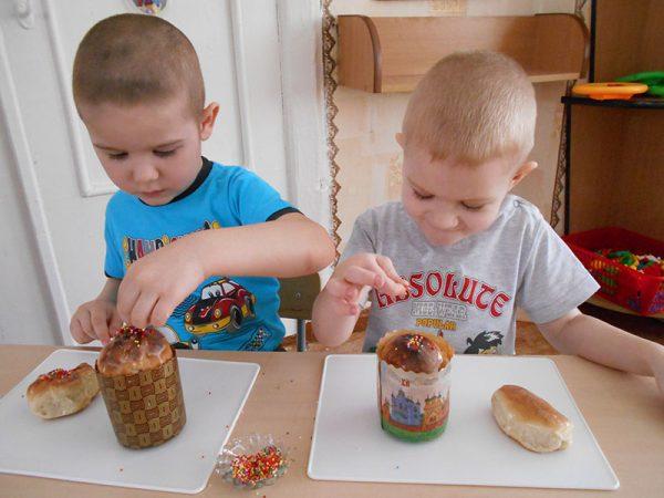 Мальчики украшают пасхальные куличи разноцветной посыпкой