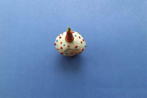 Белая глазурь украшена цветными шариками, в центре — свеча в виде жгута