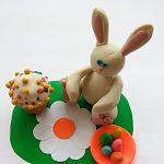Кролик на цветочной лужайке рядом с куличиком и тарелкой с яичками