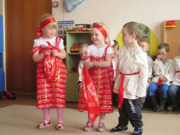 Две девочки в народных сарафанах с платочками и мальчик в рубахе