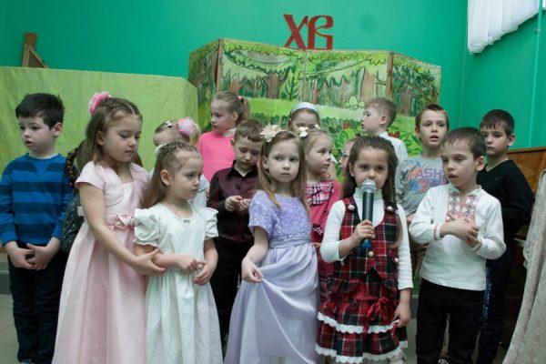 Дети на утреннике к Пасхе: девочка говорит в микрофон