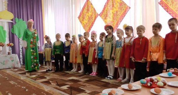 Дети и педагог в костюмах, на столе тарелки с крашеными яйцами