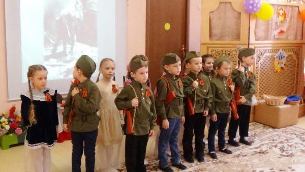 Дети в форме и слайд тематической презентации на заднем фоне