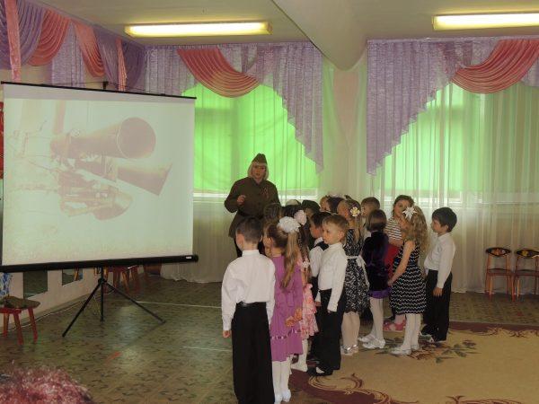 Педагог в форме показывает детям презентацию по теме
