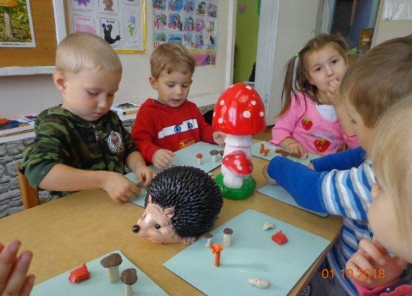 Дети лепят грибы, на столе стоит большой керамический ёжик