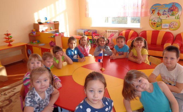 Дети сидят за круглым красно-оранжевым столом
