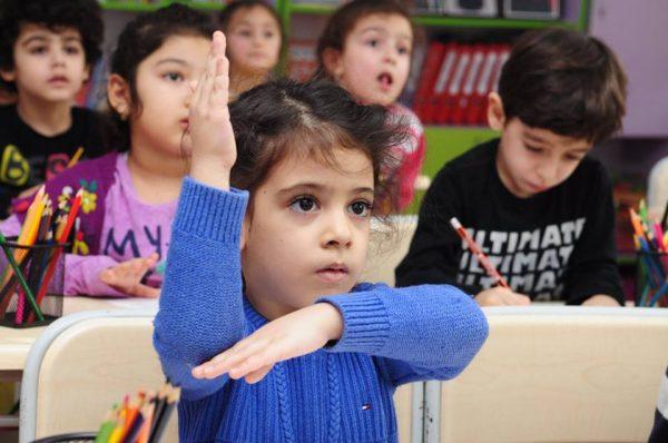 Дети за столами, девочка подняла руку